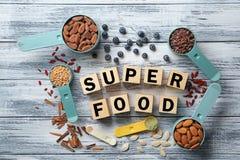 Samenstelling met kubussen en assortiment van superfoodproducten in metende lepels op houten achtergrond Stock Foto's