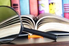 Samenstelling met open boek en vergrootglas Terug naar school, exemplaarruimte schaar en potloden op de achtergrond van kraftpapi Stock Fotografie