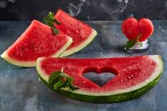 Samenstelling met rijpe watermeloen, muntbladeren en een hart dat in een plak van watermeloen wordt gesneden Concept voor valenti stock fotografie