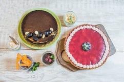 Samenstelling met smakelijke kaastaart en koppen met mousse op een houten lijst, hoogste mening Stock Afbeelding