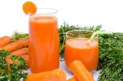 Samenstelling met twee glazen wortelsap en verse wortelen Stock Foto's