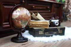 Samenstelling op een houten vloer uitstekende bol met oude leersui Stock Afbeeldingen