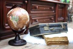 Samenstelling op een houten vloer uitstekende bol met oude leersui Stock Afbeelding