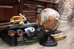 Samenstelling op een houten vloer uitstekende bol met oude leersui Stock Fotografie