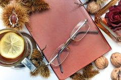 samenstelling Thee met citroen, een gesloten boek, glazen en kastanjes royalty-vrije stock foto