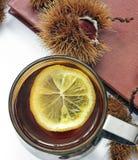 samenstelling Thee met citroen, een gesloten boek, glazen en kastanjes royalty-vrije stock fotografie