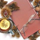samenstelling Thee met citroen, een gesloten boek, glazen en kastanjes stock foto's