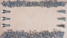 Samenstelling van bemanning en bouten bij houten achtergrond met exemplaarruimte voor uw eigen tekst stock foto's