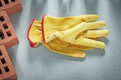 Samenstelling van de oranje handschoenen van de het leerveiligheid van bouwbakstenen stock foto's