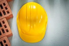 Samenstelling van de veiligheidshelm van bouwbakstenen op concrete bac stock foto