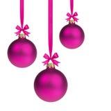 Samenstelling van drie purpere Kerstmisballen die op lint hangen Stock Fotografie