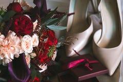Samenstelling van een huwelijksboeket van witte en rode rozen met gouden ringen met topaas, beige bruidschoenen en dozen stock foto's