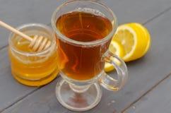 Samenstelling van een kop thee, een gesneden citroen en een kruik honing stock fotografie