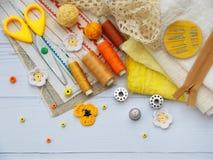 Samenstelling van gele toebehoren voor handwerk op houten achtergrond Het breien, borduurwerk, het naaien Kleine onderneming Inko stock afbeelding