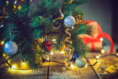 Samenstelling van Kerstboom in vaas met decoratie, giften en lichten op de houten uitstekende lijst Retro stijlkerstmis backgr stock fotografie