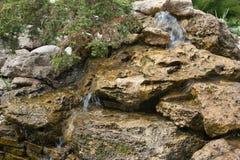Samenstelling van kleine kunstmatige waterval en stenen in park Stock Afbeelding