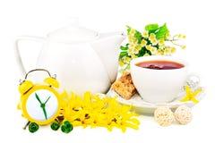 Samenstelling van kop thee, klok en de lentebloemen royalty-vrije stock afbeeldingen