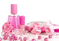 Samenstelling van roze: parfum, een kam, lint Stock Foto
