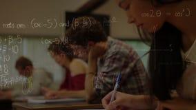 Samenstelling van studenten die met wiskundesymbolen werken in voorgrond stock footage