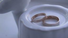 Samenstelling van twee trouwringen bij de lijst stock video