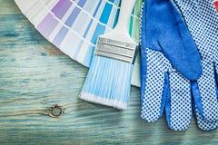 Samenstelling van van de de kleurenmonstertrekker van veiligheidshandschoenen de verfborstels op hout stock afbeeldingen