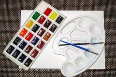 Samenstelling van waterverf sipplies, pallete en borstels stock foto's