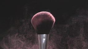 Samenstellingsborstels met roze poeder op een zwarte achtergrond in langzame motie stock video