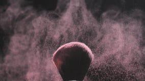 Samenstellingsborstels met roze poeder op een zwarte achtergrond in langzame motie stock videobeelden