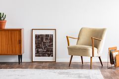 Samenvatting grafisch in houten kader tussen retro kabinet met installatie en elegante beige leunstoel, echte foto stock foto