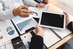 Samenwerkend in bureauconcept, jonge zakenlieden die touchpad digitale tablet gebruiken om de situatie op de markt te bespreken o royalty-vrije stock afbeeldingen
