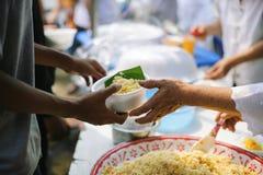 Samh?llet av att dela mat till heml?ns och det mest fattig: Begreppet av matning: H?nderna av det rikt ger mat till h?nderna av royaltyfri bild