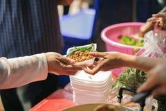 Samh?llet av att dela mat till heml?ns och det mest fattig: Begreppet av matning: H?nderna av det rikt ger mat till h?nderna av arkivbild