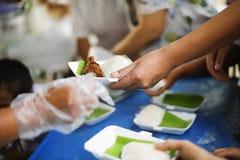 Samh?llet av att dela mat till heml?ns och det mest fattig: Begreppet av matning: H?nderna av det rikt ger mat till h?nderna av arkivbilder
