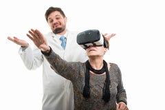 Samiec doktorski i żeński starszy pacjent z vr gogle gestykulować zdjęcie royalty free