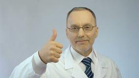 Samiec doktorski ono uśmiecha się przy kamerą, robi aprobaty ręki znakowi, najlepszy pomoc medyczna zbiory