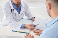 Samiec doktorski pokazuje kardiogram pacjent w klinice Fotografia Royalty Free