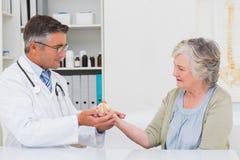 Samiec doktorski pomaga żeński pacjent trzymać ciężar Zdjęcia Royalty Free