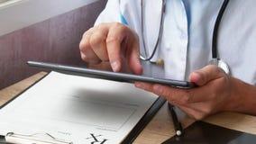 Samiec doktorski ` s wręcza używać jego nowożytnego cyfrowego pastylka komputer zbiory wideo