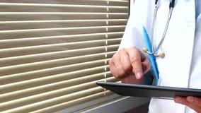 Samiec doktorski ` s wręcza używać jego nowożytnego cyfrowego pastylka komputer zbiory
