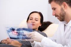 Samiec doktorski wyja?nia promieniowanie rentgenowskie pacjent zdjęcia stock