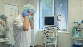 Samiec doktorskiego kładzenia chirurgicznie kapelusz dalej podczas gdy pielęgniarka myje jej ręki w operacja pokoju Zdjęcie Royalty Free