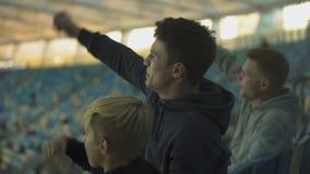 Samiec fan i dziecka falowania ręki w poparciu dla drużynę futbolową, odświętność cel zdjęcie wideo