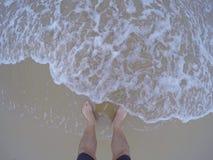 Samiec iść na piechotę na piaskowatej plaży z foamy wodą Obrazy Stock
