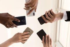Samiec i żeńskie różnorodne ręki trzyma telefony, zbliżenie pod widokiem zdjęcia stock