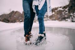 Samiec i kobieta iść na piechotę w buta stojaku w kałuży z latać w oddaleniu wodnych pluśnięcia Zdjęcia Stock