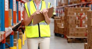 Samiec i kobiety magazynowy pracownik sprawdza zapas zbiory