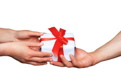 Samiec i kobiety ręki z białym prezenta pudełkiem z łękiem nad bielem Zdjęcia Stock