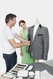 Samiec krawiecki bierze pomiar kostium podczas gdy żeńska coworker pozycja besides Zdjęcie Royalty Free
