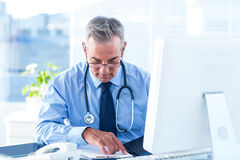 Samiec lekarka egzamininuje dokument w szpitalu Zdjęcie Stock