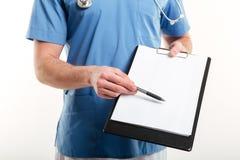 Samiec lekarka lub medyczna pielęgniarka wskazuje z piórem pustej strony schowek Fotografia Stock